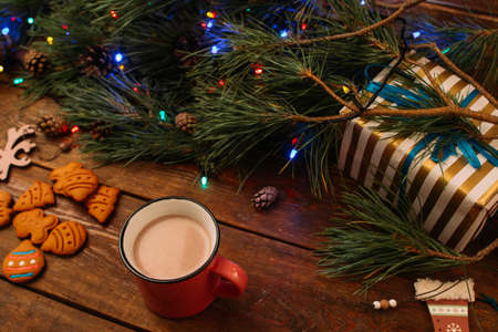 Delicious Christmas evening with latte. Pine branch with fairy lights, gift box and gingerbread cookies on wooden background, view from above. Family celebration and warm holiday concept
