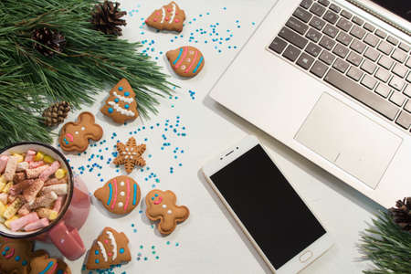 Chatting during Christmas and New Year holidays. Festive background of laptop and smartphone near pine and cup of marshmallows with cookies, top view. Greetings in social network concept