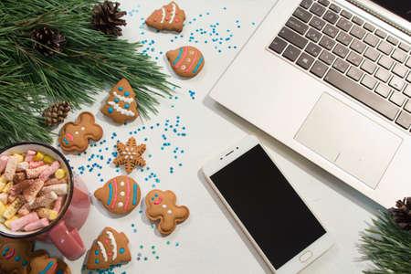 Chiacchierando durante le feste di Natale e Capodanno. Fondo festivo del computer portatile e dello smartphone vicino al pino e tazza di caramelle gommosa e molle con i biscotti, vista superiore. Saluti nel concetto di social network Archivio Fotografico