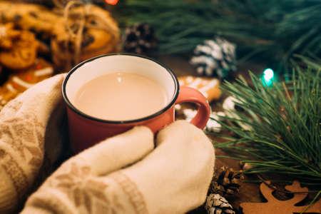 라 떼와 쿠키와 따뜻한 크리스마스 휴가입니다. 가 까이 서 니트 장갑에 술 한잔과 함께 인식 할 수없는 여자 축제 배경에 손을. 축제 및 박람회 개념에 스톡 콘텐츠