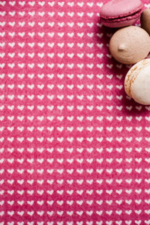 Lovely composition of macaroons. Sweet colorful cakes on heart figured cloth, top view. Love of desserts and sweets concept