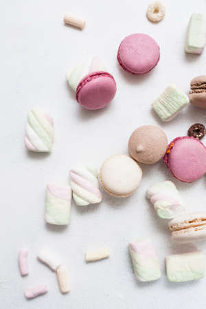 Top view colorful sweets on white background. Delicious macaroons, zephyrs and breakfast cereal are spread around, close up Stock Photo