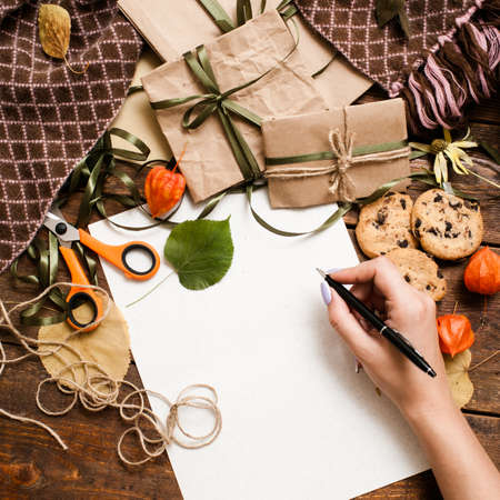 Autumn holidays and preparing presents, top view. Unrecognizable woman writing check list on wooden table near small wrapped gifts, chocolate cookies, scissor and bands laying on warm cozy plaid Stock Photo