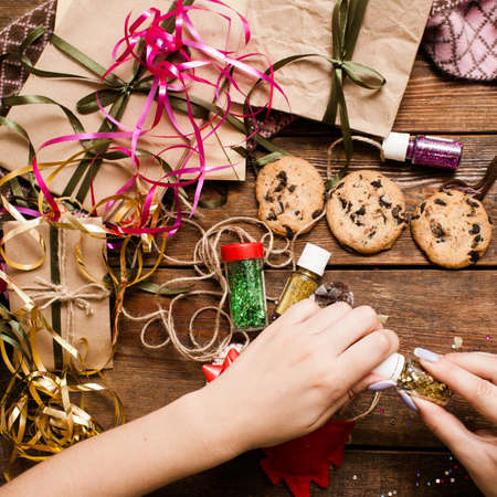 Preparing gifts for Christmas holiday, top view. Unrecognizable woman uses glitters for decoration. Wrapped small presents on wooden table near ornaments, chocolate cookies and bands