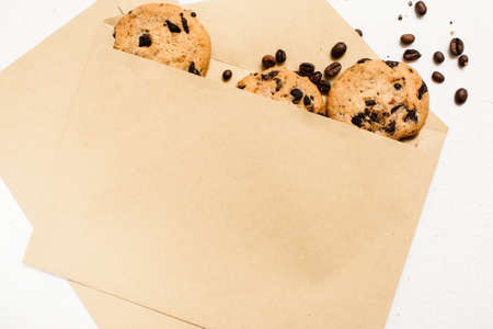 Fond of sweets and bakery shops concept. Small elegant presents with home-baked chocolate scones and coffee seeds decoration on white background, top view close up