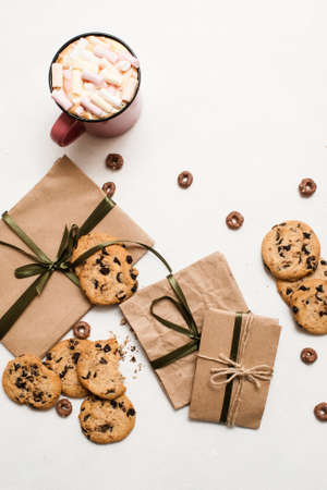 Preparing gifts with sweets and cup of latte. Small elegant presents on white table with homemade chocolate scones and delicious hot drink with marshmallow, top view picture Imagens