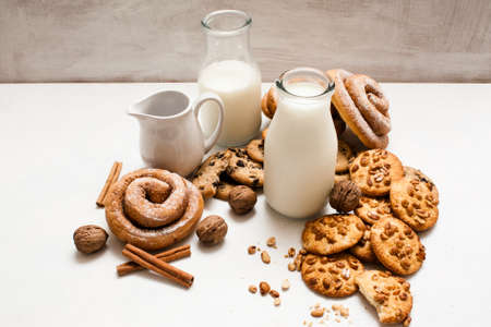 Culinary background of home-baked shop. Wholegrain scones, baked rolls,walnuts and spices laying near bottles of milk on white table. Concept of delicious rustic breakfast with cookies