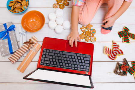 Creative leisure time on New Years day. Unrecognizable girl watching Christmas cartoons, laptop with white screen mockup. Festive decorations on wooden background top view Stock Photo