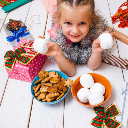 Miracle for child. Christmas celebration. Favorite time of year. Joyful girl with tasty sweets on wooden background. Yummy presents. Happiness concept