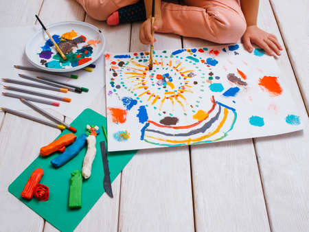 Young artist. Early children education. Unrecognizable artistic child on white background, colorful drawing process. Creative art studio, creativity concept