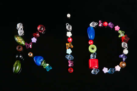 Colorful beads on black background, top view. Handmade kid creativity, making words and accessories design beading