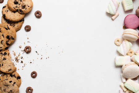 Sweet colorful background with free space. Wholegrain chocolate scone, macaroons and marshmallow top view, culinary art of homemade pastry, sweet bakery concept Imagens