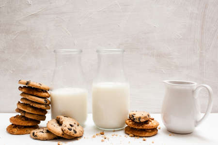 Wholegrain products eating with milk, close up. Chocolate scones in one line with bottles and pitcher of lacto drink. Home-baked shop concept