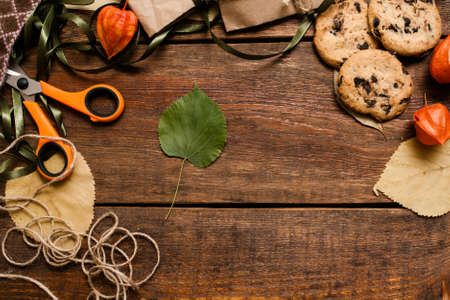 Autumn festive background top view. Chocolate cookies with partially seen small gifts, scissor and bands laying on wooden table with free space in the middle