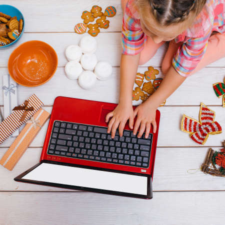 Leisure time on New Years day. Little girl watching Christmas cartoons, laptop with white screen mockup. Festive decorations on wooden background top view. Festivity concept