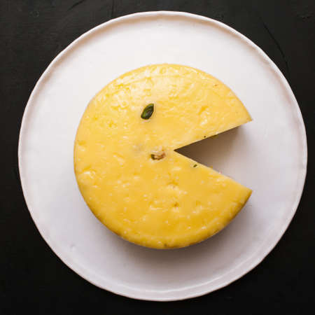Homemade gourmet cheese. Healthy food. Pacman concept from quality sort of Caciotta with pistachio, close up top view