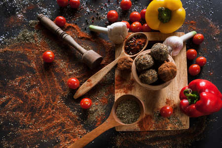Spicy cheese assortment. Healthy rustic food with free space. Gourmet sorts of dairy with spices and vegetables on black background, recipe and menu concept