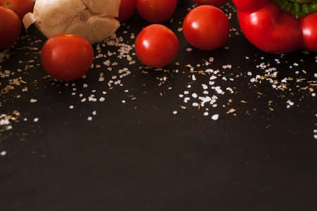 Food background of fresh vegetables, close up. Spicy ingredients and cherry tomatoes on black table, free space beneath Stock Photo