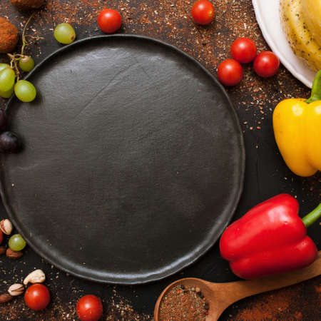Healthy food and empty plate top view. Close up background of vegetables and spices, free space black dish. Recipe, cuisine and menu concept Stock Photo