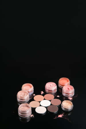 Professional set of cosmetics on black background, free space above. Neutral colors for nude make up