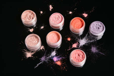 Professional set of cosmetics on black background, close up top view. Powdery eyeshadow, pigments and colourants for natural make up