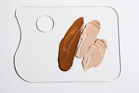 Cosmetic foundation different shades swatch on palette on white background, close up. Professional make up product for face and concealer samples