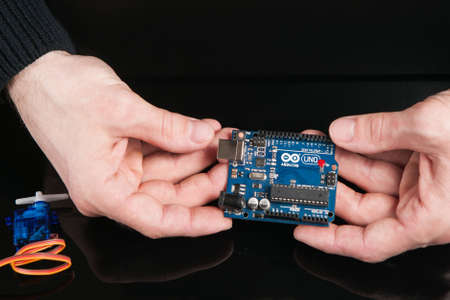 Kharkov, Ukraine - March 21, 2017: Arduino UNO board holding in engineer hands on black background, close up. Microcontroller for programming and prototyping Editorial