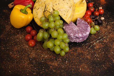 Cheese assortment. Healthy rustic food. Dairy milk products, free space. Variety of vegetables around Stock Photo