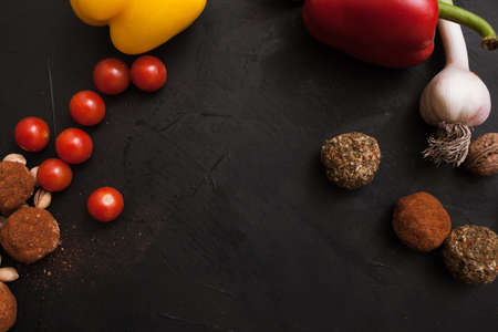 Spicy cheese assortment. Healthy rustic food with free space. Gourmet sorts of dairy with cherry tomatoes on black background