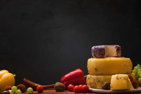 Gourmet sorts of cheese with variety of vegetables, fruits and spices on black background. Still-life composition of luxury products, close up, free space. Rustic local dairy advertisement