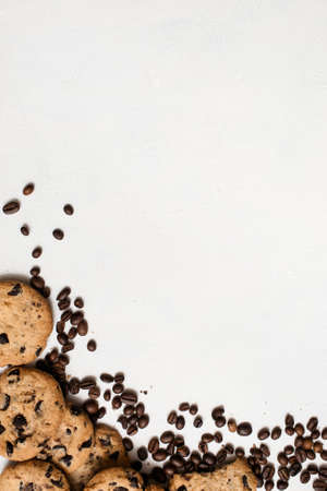 Wholegrain chocolate scone with coffee grains on white background, top view with free space. Delicious cookies and culinary art of coffeehouse concept Imagens