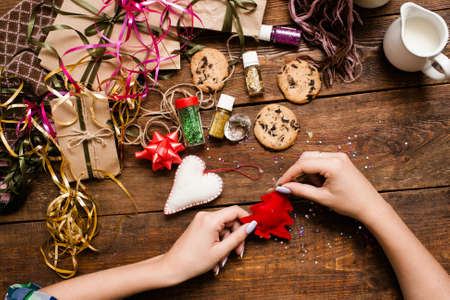 Decoration for winter holidays, top view. Unrecognizable woman makes red felt fir tree on wooden table near many other Christmas ornaments, cookies and gifts. Happy celebration concept