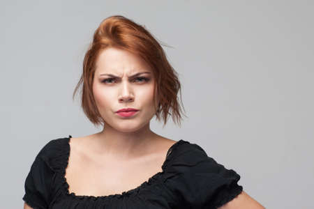 Suspicion in adultery. Angry woman jealousy. Distrust in relationships, grumpy female mood on grey background. Personal life problems, suspicious concept