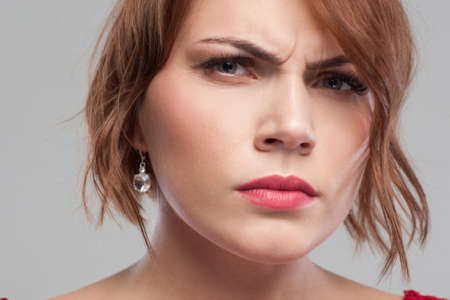 Suspicious look. Distrust in partner. Relationships problems, angry female portrait on grey background closeup, suspicion concept