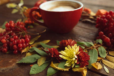 Cup of hot latte on the autumn background. Fall bouquet on the wooden rough surface.