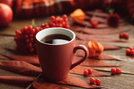 Hot beverage to keep warm in autumn. Black coffee or tea concept. Fall leaves background
