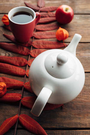 Hot drink on a cold autumn day in a white teapot. Warmth and coziness concept Stock Photo