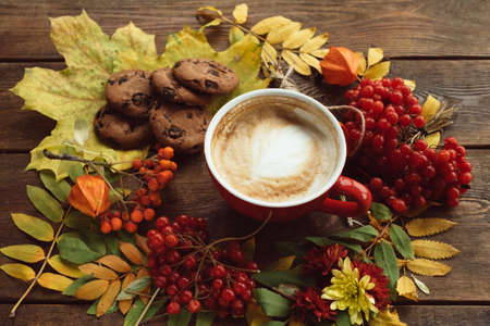 Cup of hot latte and cookies on the autumn background. Fall bouquet on the wooden rough surface. Stock Photo