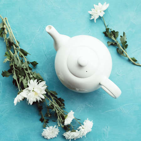 Herbal tea and chrysanthemums on a blue background. Healthcare lifestyle. Pure and tenderness.