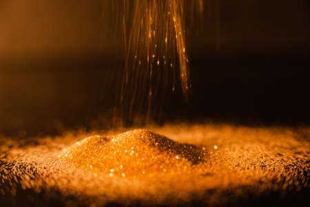 Pouring abstract gold glitter background. Precious metal concept Фото со стока