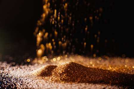 Shimmering abstract gold background. Flowing glitter. Rich and luxury concept