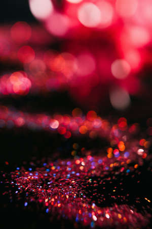 Multicolor glitter on black contrast background. Defocused bokeh blur flares concept Stock Photo