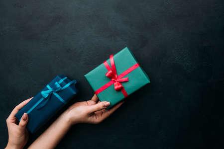여자 손 선물 상자를 들고입니다. 남자에게 완벽한 선물을 고르는 문제. 가치있는 보상 개념