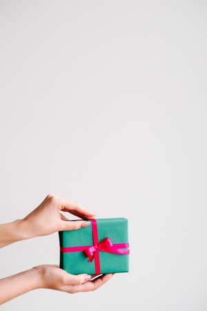 presenting an elegant gift on dark background. closed gift box wrapped of ribbon and a bow. pleasant surprise for birthday, new year, christmas, valentines day and other holidays.