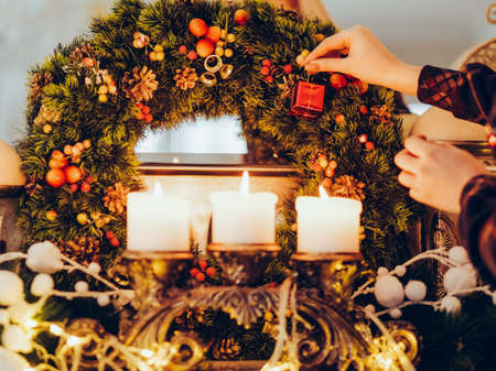 festive decoration preparing home coziness concept. christmas wreath and candles light. magic of winter holidays.
