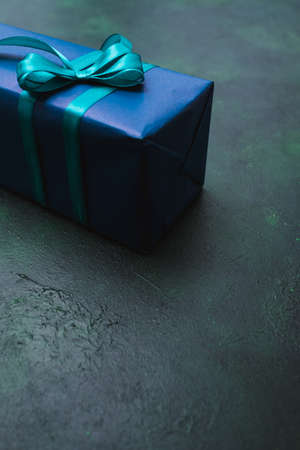 Gift for a man in a stylish modest wrapping on dark background. Free space concept