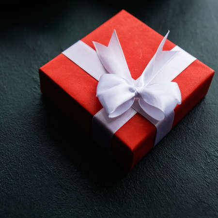 Red gift box with a present for someone special. Love affection worthy reward concept