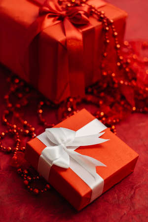romantic women gift box with wrapped ribbon on red background. present for beloved on birthday, christmas, new year, thanksgiving, valentines day and other holidays. color of passion Stock Photo