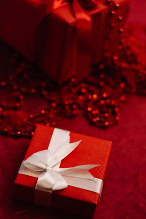 romantic women gift box with wrapped ribbon on red background. present for beloved on birthday, christmas, new year, thanksgiving, valentines day and other holidays. color of passion Reklamní fotografie