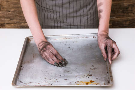 No dinner today. Kitchen cooking fail. Woman hands cleaning dirty baking pan